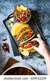 Chili con carne tacos, held by a person, homemade delicious meal served on a dark plate on a blue textured background view from the top