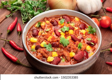 Chili con carne, a traditional Mexican dish with red beans, cilantro leaves, ground meat, and chili peppers, a closeup with ingredients