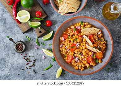 Chili con carne of turkey  with chickpeas served with nachos.  Chili with meat, nachos, lime, hot pepper. Mexican / Texas traditional food. Top view