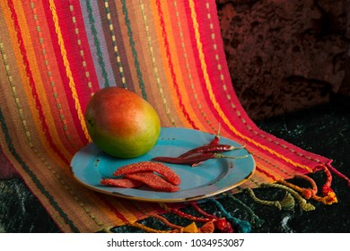 Chili lime mango slices with dried chilis and fresh mango on a rustic blue plate and colorful  Mexican Print placemat