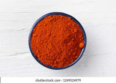 Chili paprika powder in cast iron bowl on white wooden background, view directly from above.