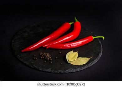 chili pepper, black pepper and bay leaf on a black background