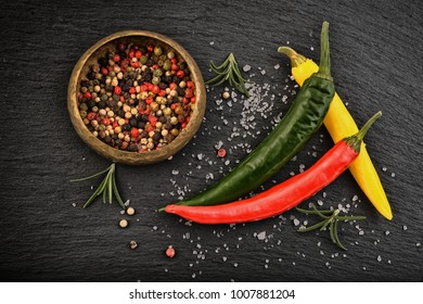 Chili and pepper, black stone table - background