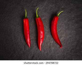 the chili pepper on black stone background, still life style