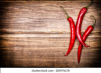 Chili pepper on the wooden background.