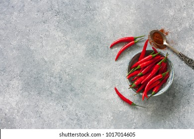 Chili peppers in clay pot over blue stone background. Top view. Copy space