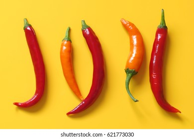 Chili peppers orange and red on yellow background