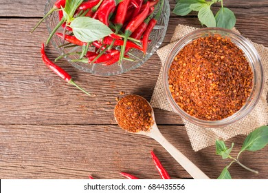 Chili powder and flakes with red chili pepper on wood background. Top view.