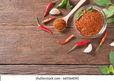 Chili powder and red chili pepper on wooden background. Top view.