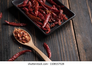 Chili powder in a wooden spoon and dried chili in ceramic plate on old black stained wooden table. Selective focus