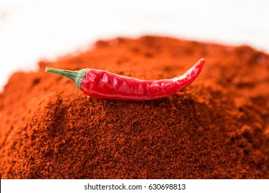 chili red hot pepper, concept of popular spice - delicious juicy pod of chili red pepper is isolated on top of red curry powder, ground dried idnian famous blend