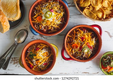 Chili with shredded cheese in colorful bowls