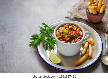 Chili soup in gray mug. Stone background,selective focus. Place for text.