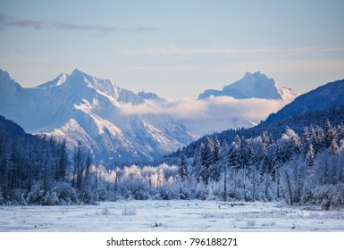 Chilkat mountains in Southeast Alaska with frost on the trees and a streak of low clouds near sunset.