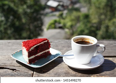 Chill with Black coffee in white cup and Red Velvet cake on blue plate on the wooden table from natural morning background