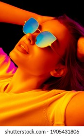 Chill. Caucasian woman's portrait on black studio background in orange-pink neon light. Beautiful female model with blowing hairs out. Concept of human emotions, facial expression, sales, ad, fashion.