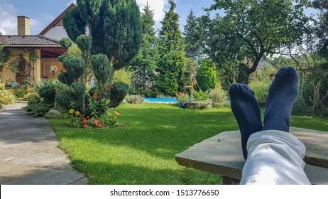 Kühl in der Natur. Entspannen Sie sich im Garten mit Füßen auf dem Tisch.