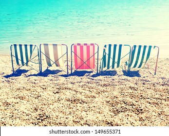 chill on beach with retro stripes sun bed / cross processing style
