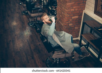 Chill out at the barber shop. Side view of handsome stylish young red bearded man drinking beer, while waiting to get a haircut