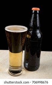 Chilled beer bottle and glass with water droplets on