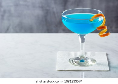 Chilled Blue Lagoon or Blue Hawaii Cocktail with Orange Twist in Goblet on Marble Bar Table
