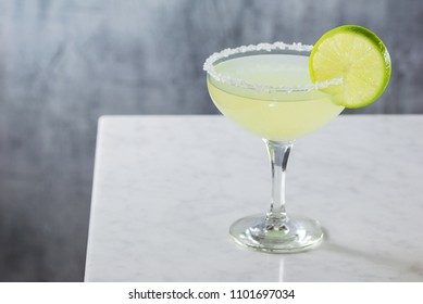 Chilled Margarita Cocktail in Goblet with Salted Rim on Marble Bar Counter