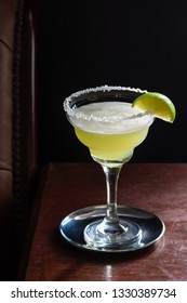 Chilled Margarita Cocktail Served Straight Up with Salted Rim in Dark Luxurious Bar