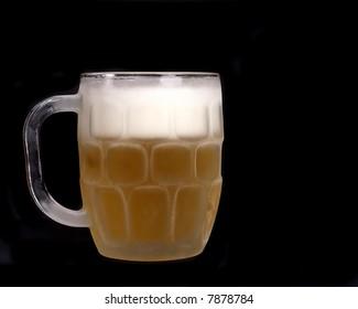 Chilled mug of beer on a black background