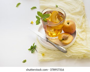 Chilled peach tea in glass with fresh cut peaches on white background. Text space image.