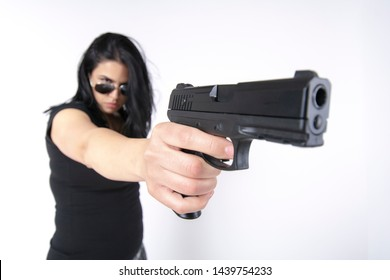 Chilled and relaxed gangster lady with sunglasses on shooting with a handgun, white background, studio image