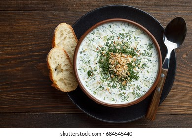 Chilled tarator with bread and spoon on wooden table ready to eat. Healthy summer refreshment soup with vegetables. Top view with copy space.