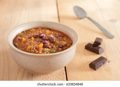 Chilli con carne. Beans, tomatoes, bell pepper, onion, garlic, chocolate. Bowl on wooden table.