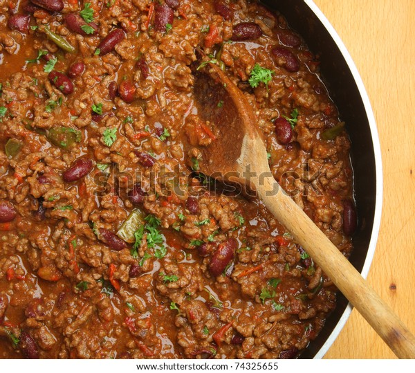 Chilli con carne being stirred with wooden spoon.