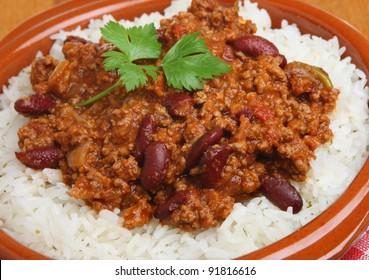Chilli con carne with rice in terracotta dish.