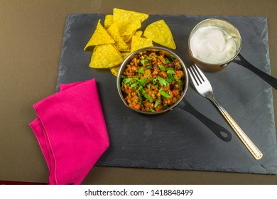 Chilli con carne with scattered parsley served with soured cream and tortilla chips in serving pan with fork, red napkin.