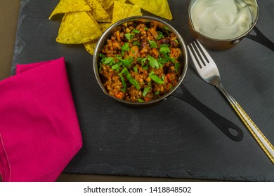 Chilli con carne with scattered parsley served with soured cream and tortilla chips in serving pan with fork, landscape.