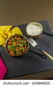 Chilli con carne with scattered parsley served with soured cream and tortilla chips in serving pan with fork, portrait.