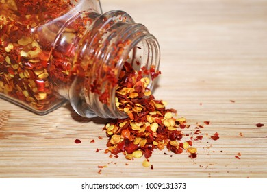Chilli Flakes Spilling Out of Glass Jar on Wooden Chopping Board