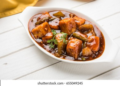 Chilli paneer or Spicy cottage cheese, served in white Dish with capsicum and onion, favourite indian starter menu, selective focus