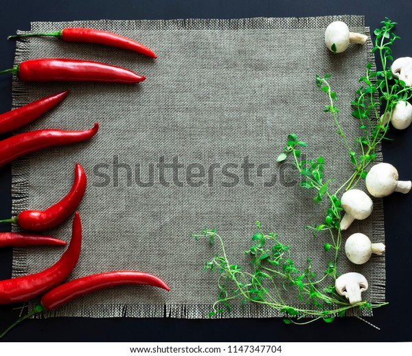 chilli pepper and mushrooms on a black background with textile
