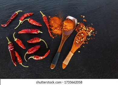 Chilli, red pepper flakes and chilli powder on slate. Spicy food. Hot spices.