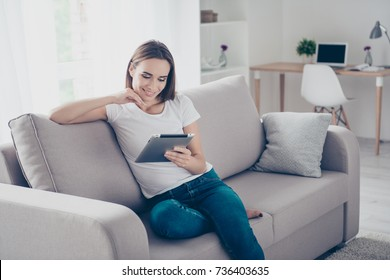 Chilling gorgeous brown haired freelancer on the beige couch at home doing online shopping, so comfortable, in fashioanble white outfit, denim pants, so nice light design interior indoors