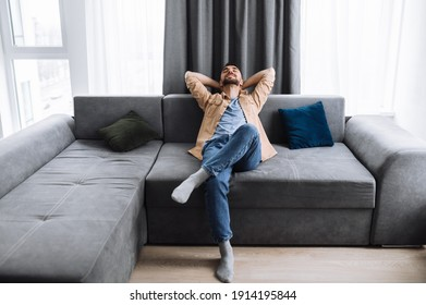 Chilling at living room. Satisfied handsome caucasian man is sitting on the couch at home, thinking about plans for weekends or vacation, with closed eyes and smiles