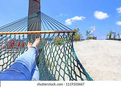 Chilling / relaxing in the green hammock on white sandy beach in San Diego. The view on girl's feet with the beach and sea in the background.