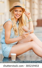 Chilling with some tunes. Smiling young woman in headphones holding mobile phone and looking at camera while sitting outdoors