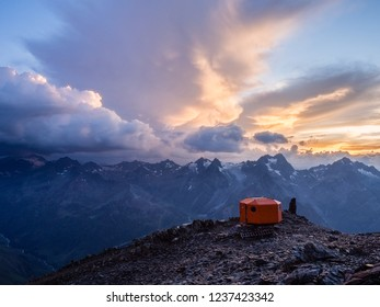 The chilling time on top of the mountain range in Austrian Alps with tourist shelter during the sunset