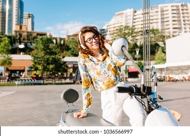 Chilling young lady in vintage blouse with floral pattern sitting on moped and listens music with trees and skyscrapers on background. Stylish girl with dark-brown curls wears glasses and earphones.