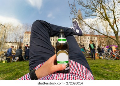 Chilling/relaxation concept. Young man in the park with bottle of lager beer