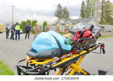 CHILLIWACK, BC - April 25, 2020: A stretcher stands ready as fire crew arrive at 46280, Second Ave., in Chilliwack, BC, Canada. High winds quickly engulfed the home believed occupied by squatters.