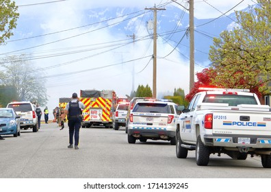 CHILLIWACK, BC - April 25, 2020: Smoke billows across the street as fire and police respond to a house fire at 46280 Second Ave., in Chilliwack, BC, Canada. The fire was treated as suspicious.